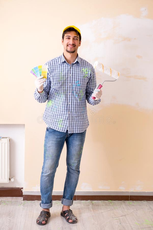 Malarza mężczyzna maluje ścianę w domu zdjęcia stock