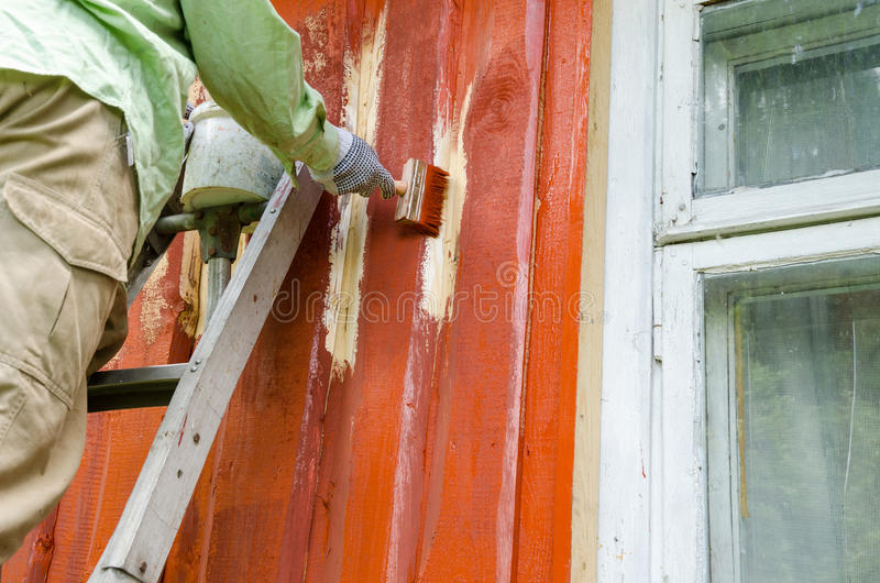 Malarza mężczyzna na drabinowej farby domu drewnianej ścianie obrazy royalty free