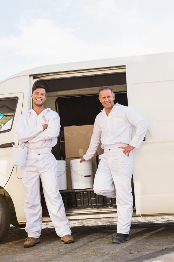 Malarzi uśmiecha się opierać przeciw ich samochodowi dostawczemu zdjęcia royalty free