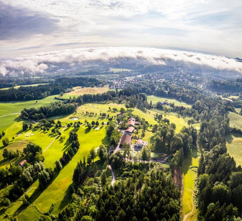 Malas montañas bávaras aéreas de Toelz Campo de golf Montaña de Blomberg Tiro del abejón de la mañana con algunas nubes en el cie imagen de archivo libre de regalías
