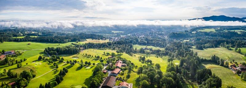 Malas montañas bávaras aéreas de Toelz Campo de golf Montaña de Blomberg Tiro del abejón de la mañana con algunas nubes en el cie imagenes de archivo