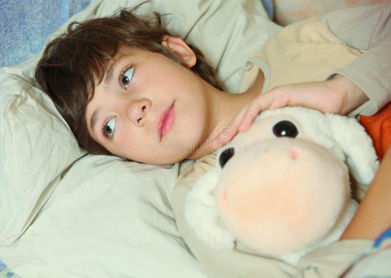 Malato bello del ragazzo del Preteen a letto con il giocattolo immagine stock