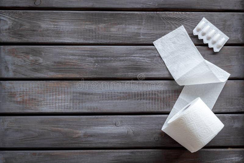 Malattia del concetto dei due punti con il rotolo della carta igienica e la supposta rettale sul modello di legno di vista superi fotografie stock libere da diritti