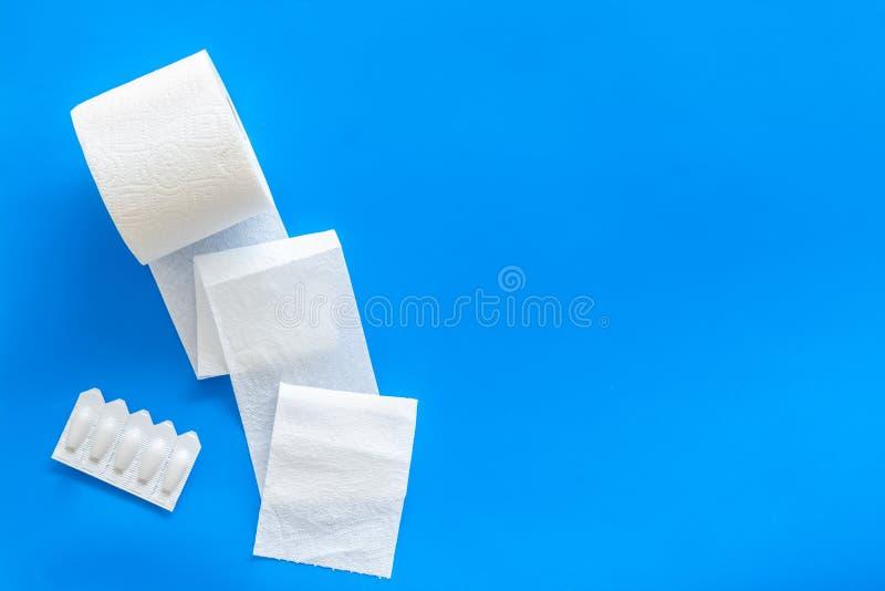 Malattia del concetto dei due punti con il rotolo della carta igienica e la supposta rettale sullo spazio blu di vista superiore  immagine stock