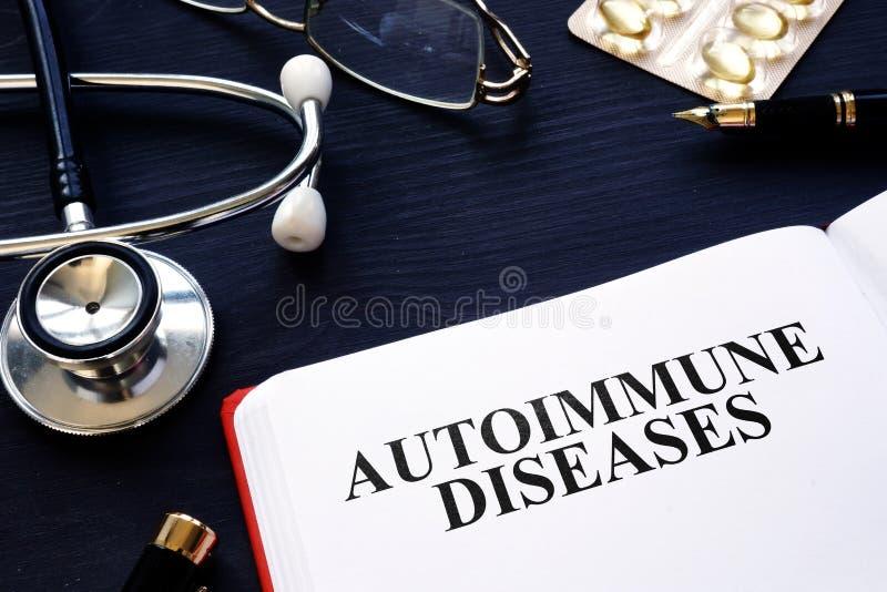 Malattie autoimmuni Libro, pillole e stetoscopio sullo scrittorio immagini stock libere da diritti