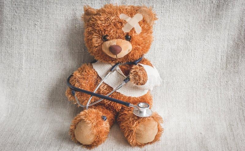 Malattie infantili dell'orsacchiotto di concetto al fondo del tessuto immagini stock libere da diritti