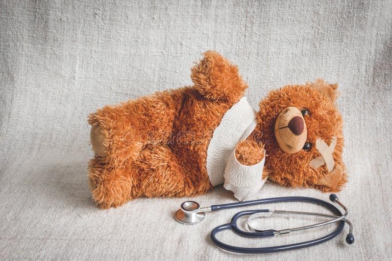 Malattie infantili dell'orsacchiotto di concetto al fondo del tessuto fotografia stock libera da diritti