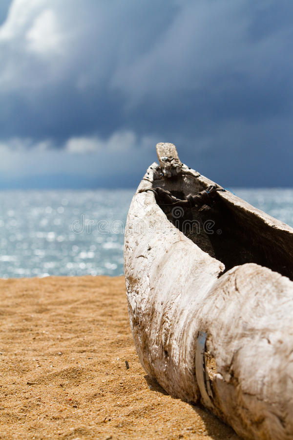 Malawian dugout. A locally made dugout canoe on a sandy beach in Malawi stock image