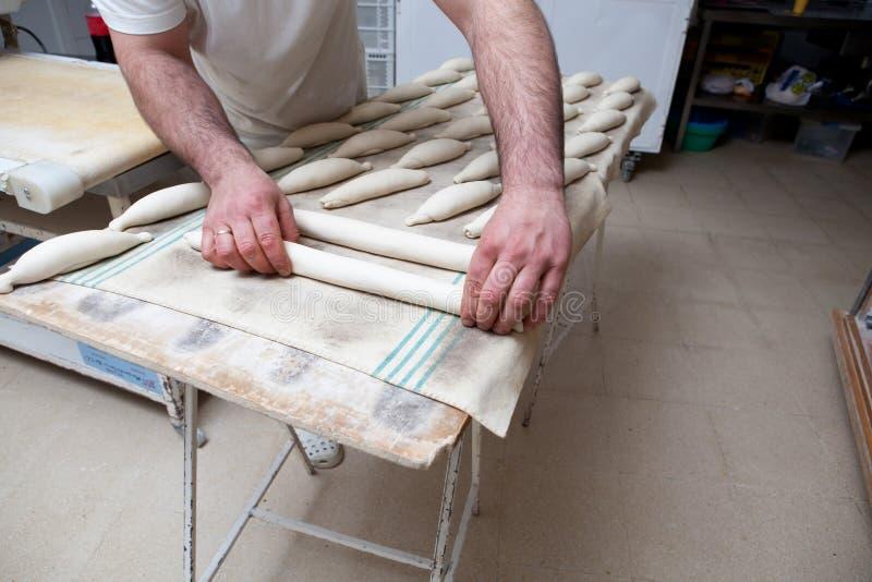 Malaxant et plaçant des morceaux de pain au-dessus de table de fermentation images libres de droits