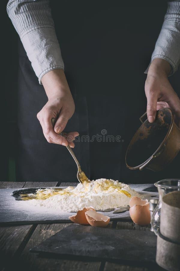 Malaxez la pâte par les mains femelles photos stock