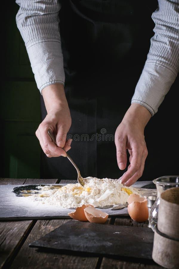 Malaxez la pâte par les mains femelles image libre de droits