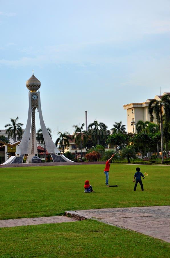 Malay ягнится бадминтон игры в поле на садах Dataran с башней с часами Ipoh Perak стоковые фото
