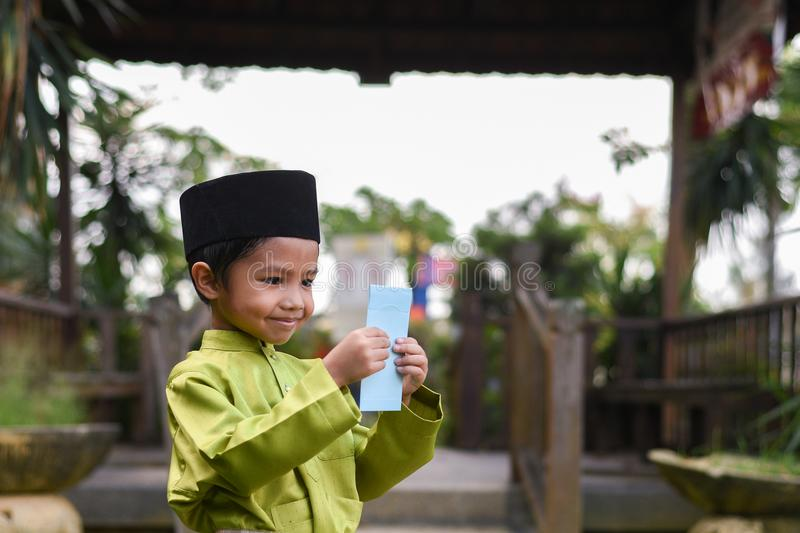 A Malay boy in Malay traditional cloth showing his happy reaction after received money pocket during Eid Fitri or Hari Raya celebr royalty free stock images