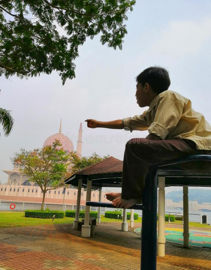 A malay boy pointing at Putra Mosque while sitting at the playground stock photo