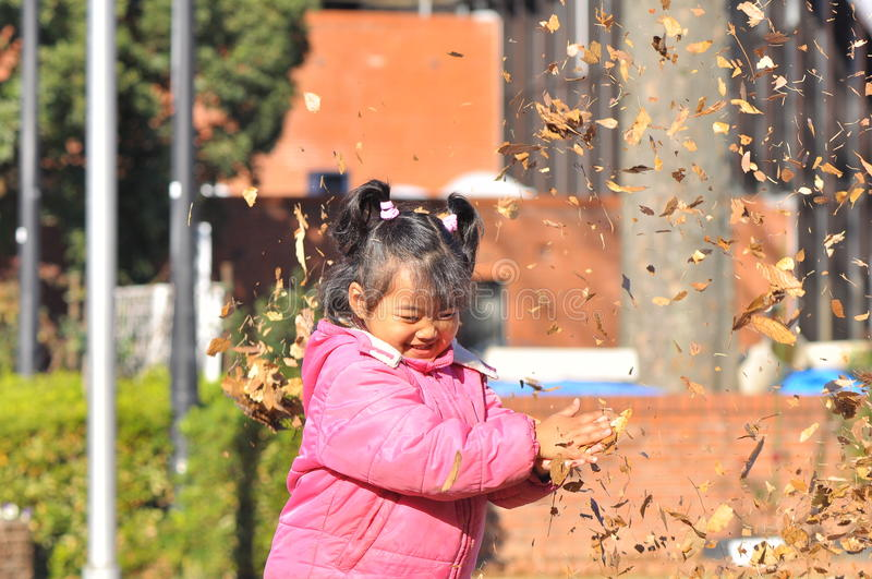 A Malay girl play with dry leaves