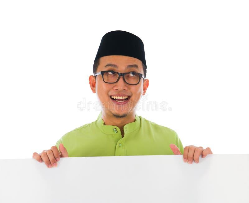 Malay male with blank card during hari raya Eid al-Fitr celebration. Photo stock photography