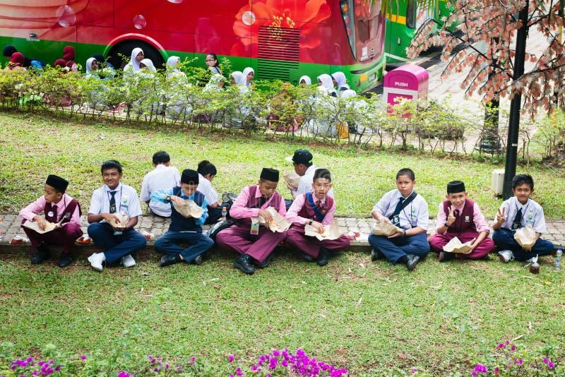 Malay muslim children have a lunch on a grass in Kuala Lumpur, M. KUALA LUMPUR, MALAYSIA - 31 OCT 2014: Malay muslim children have a lunch on a green grass lawn stock photo