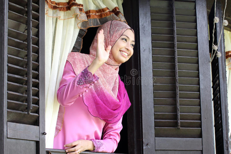Malay muslim woman wavings hand royalty free stock photo