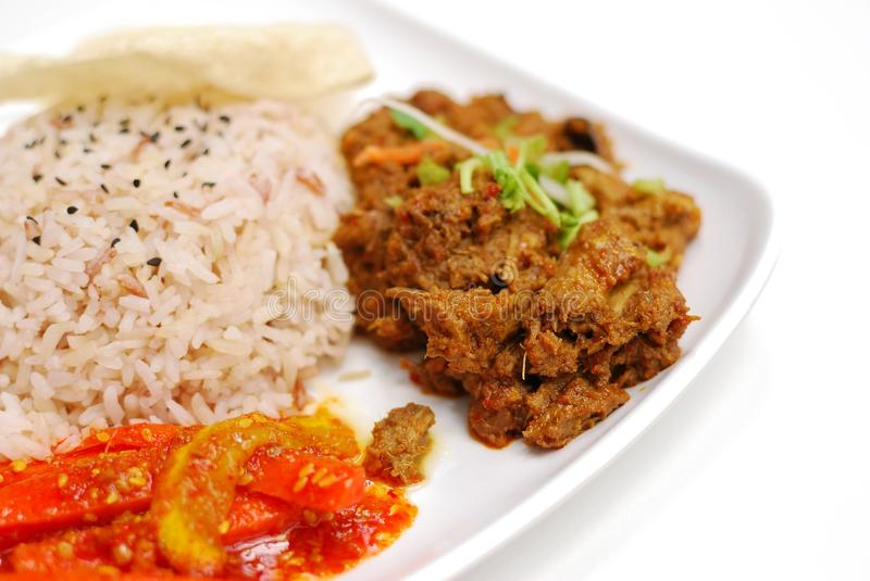 Malay vegetarian rendang chicken or mutton rice. Vegetarian rendang chicken or mutton with unpolished red rice. Rendang is also known as Malay curry. Suitable stock photo