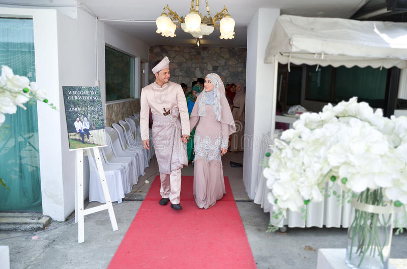 Malay Wedding Ceremony. A Malaysian couple newlywed holding hands stock photography