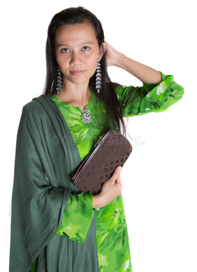 Malay Woman With A Brown Purse III. Asian Malay woman in a green dress with a brown purse over white background stock image