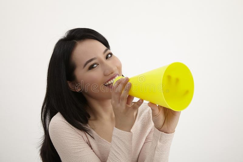 Speak out. Malay woman using megaphone on the white background royalty free stock photography