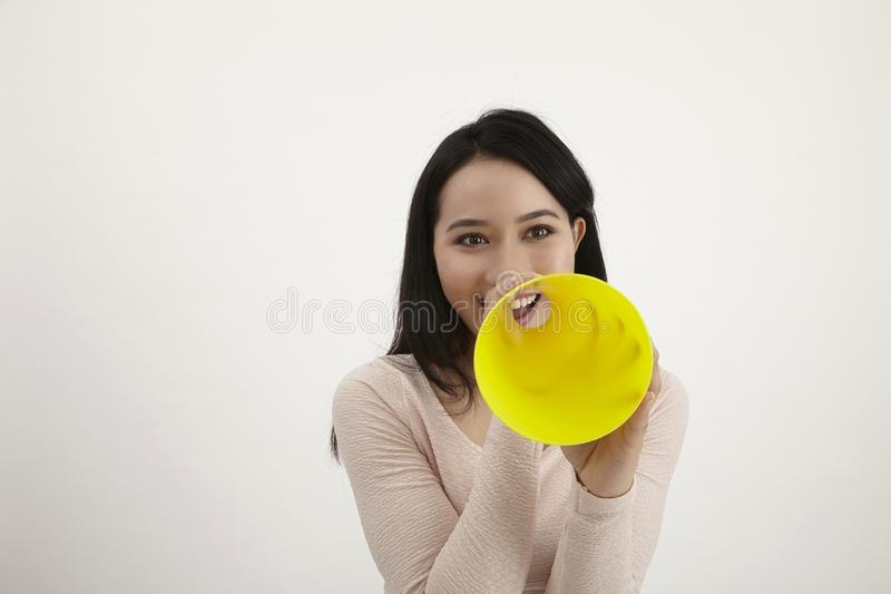 Speak out. Malay woman using megaphone on the white background royalty free stock photo