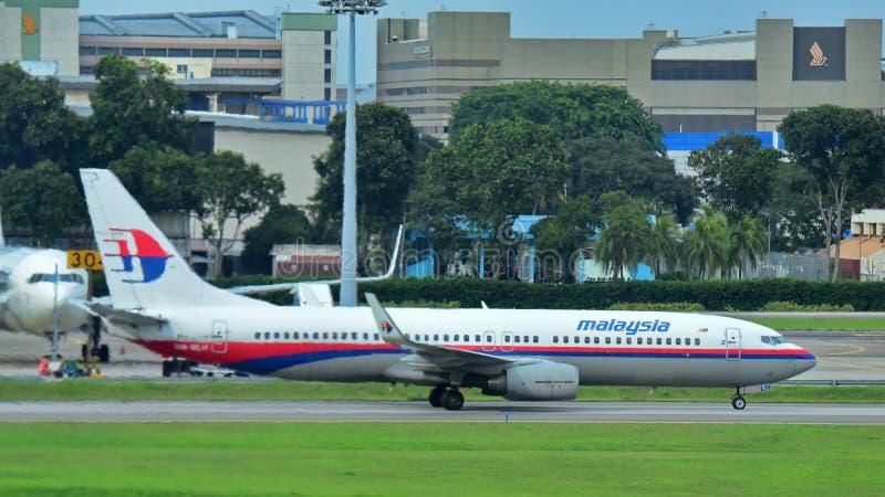 Malaysia Airlines Boeing 737 som åker taxi på den Changi flygplatsen arkivbilder