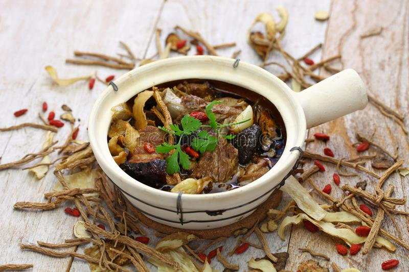 Malaysia bak kut teh, traditional chinese herbal pork ribs soup. Isolated on wooden background royalty free stock photos
