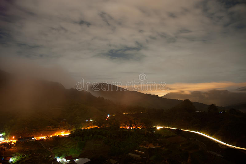Malaysia.Cameron Highlands by evening. Lit road among hills and valley floating in the mist the highlighted by lanterns.Horizontal view stock image