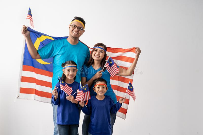 Malaysia family with attributes and flag celebrating stock photos