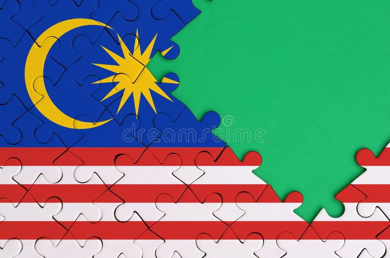 Malaysia flag is depicted on a completed jigsaw puzzle with free green copy space on the right side royalty free illustration