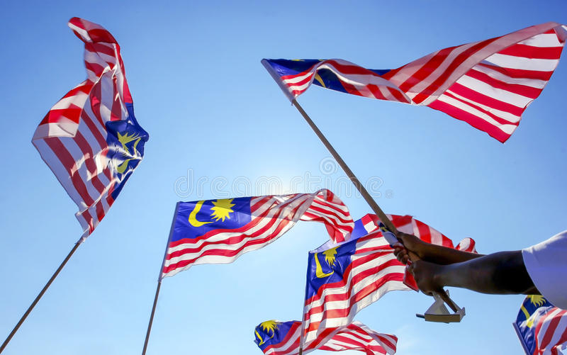 Malaysia Flag. Hand waving Malaysia flag also known as Jalur Gemilang against the blue sky. Every year in August the government of Malaysia urged people to fly royalty free stock photography