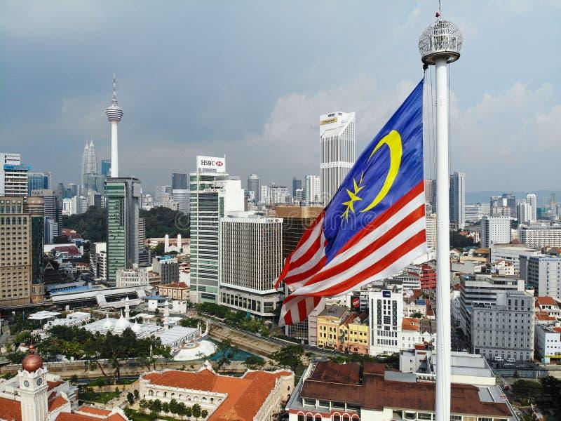 Malaysia flagga som vinkar med cityscapebakgrund royaltyfria bilder