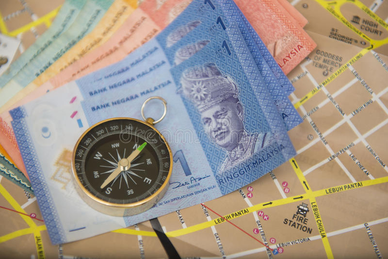 Malaysia-Geldbanknoten auf Karte mit Kompass stockbilder