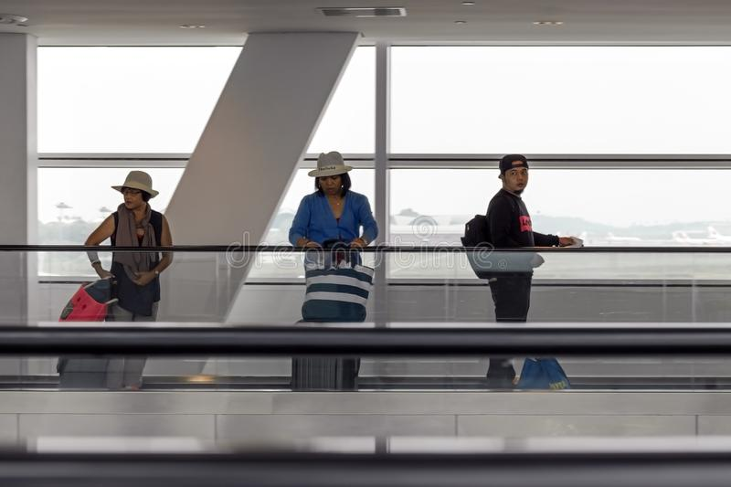 People with luggage at the airport on a moving passenger tape. royalty free stock photos