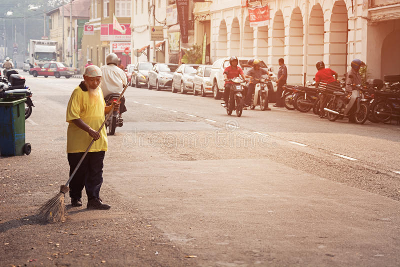 MALAYSIA, PENANG, GEORGETOWN - CIRCA JUL 2014: Old man sweeping. The streets with a coarse, handmade broom as light traffic passes on the roadway stock photo
