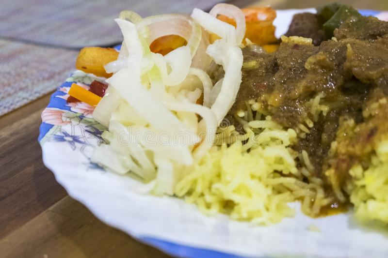 Malaysian East cost famous yellow rice. Served with pineapple salad and beef stew stock images