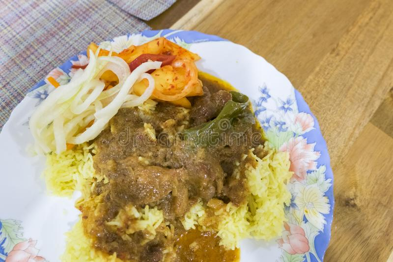 Malaysian East cost famous yellow rice. Served with pineapple salad and beef stew stock image