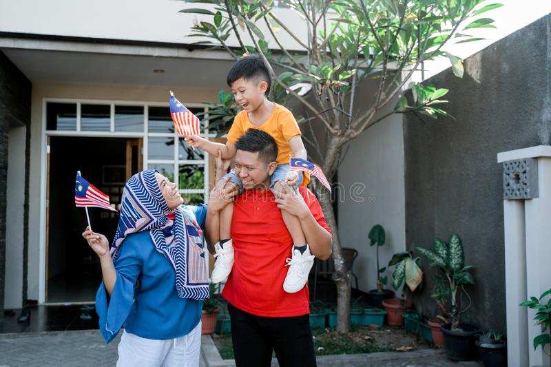 Malaysian family holding malaysia flag in front of their house royalty free stock images