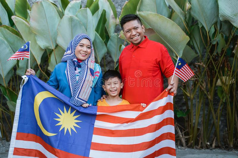 Malaysian family holding malaysia flag in front of their house stock photo