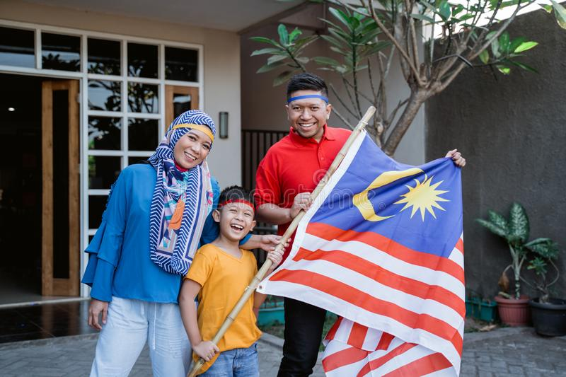 Malaysian family holding malaysia flag in front of their house royalty free stock photo