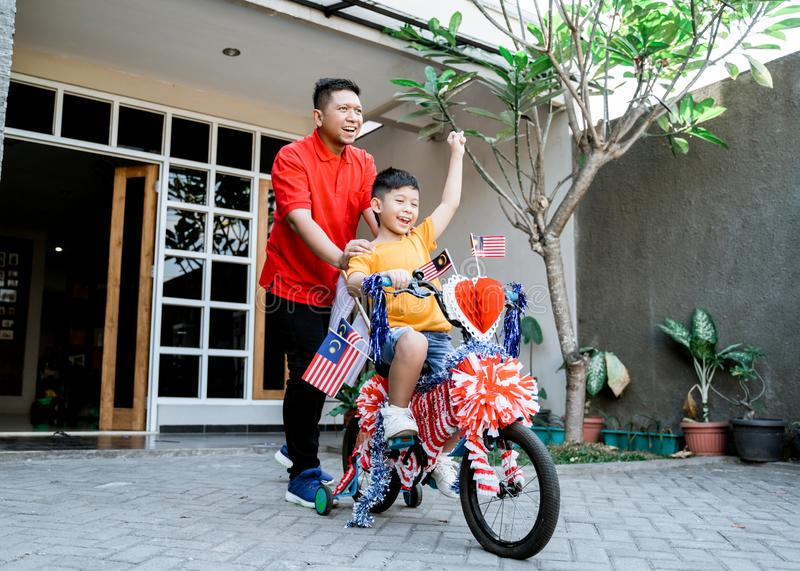 Malaysian family on malaysia independence day with basikal hias stock photography