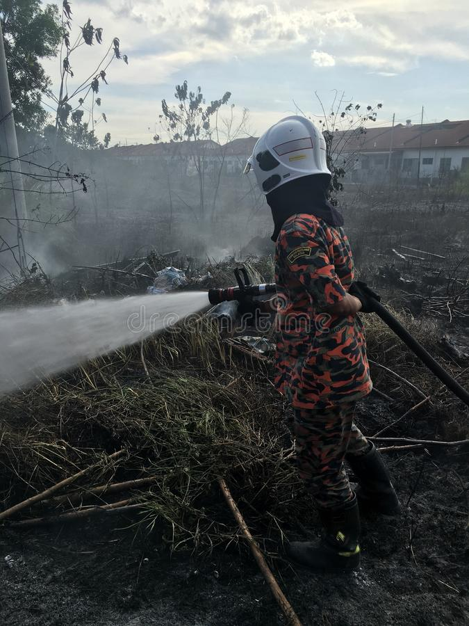 Malaysian Fire Resque Department in Action. Malaysian firefighters are putting out the fire using water royalty free stock photos