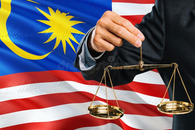 Malaysian Judge is holding golden scales of justice with Malaysia waving flag background. Equality theme and legal concept stock photos