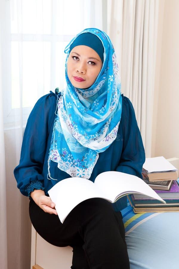 Malaysische moslemische Frau, die eine entspannende Zeitlesung genießt stockfoto
