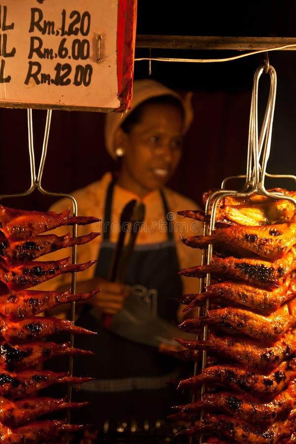 Malaysischer Verkäufer, der Hühnerflügel in einem Lebensmittel verkauft stockfotos