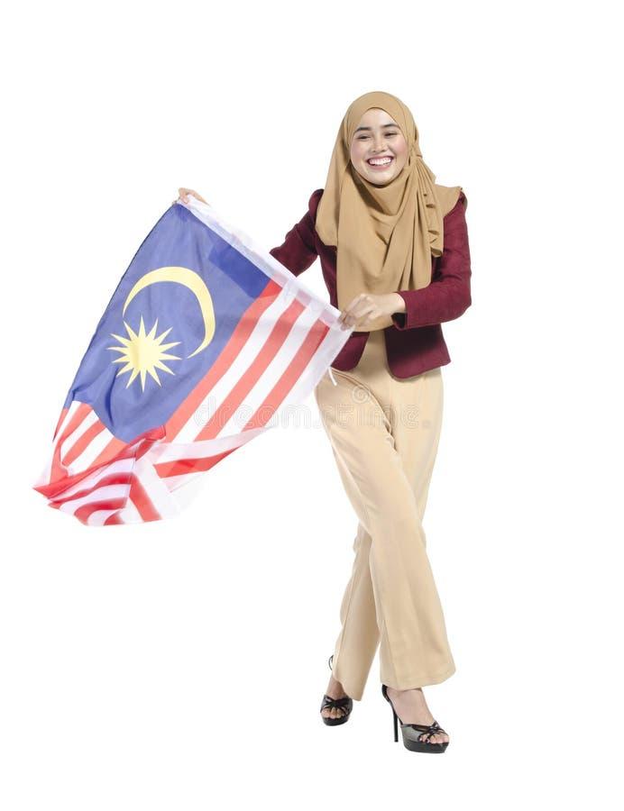 malaysischer Zivilist mit dem glücklichen Gesicht, das Flagge hält stockfotografie