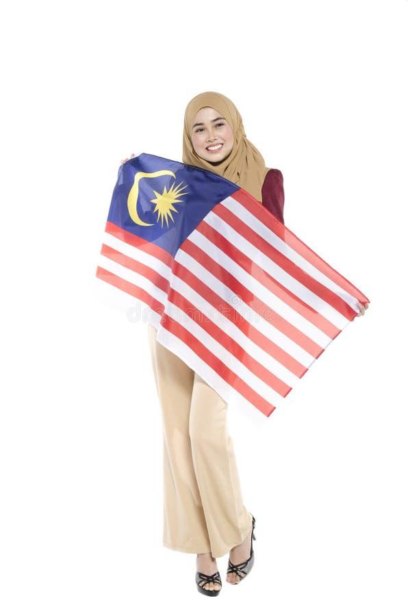 malaysischer Zivilist mit dem glücklichen Gesicht, das Flagge hält stockfoto