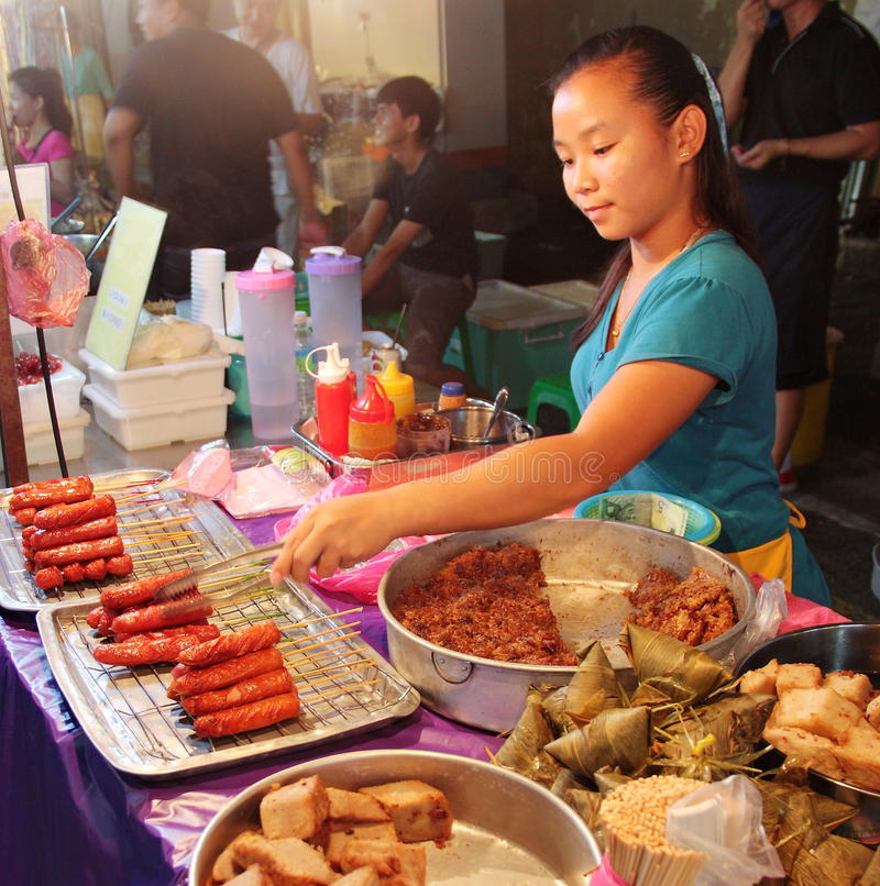 Malaysisches Mädchen, das lokale Snäcke am Nachtstraßenlebensmittel in Malakka Malaysia verkauft lizenzfreie stockbilder